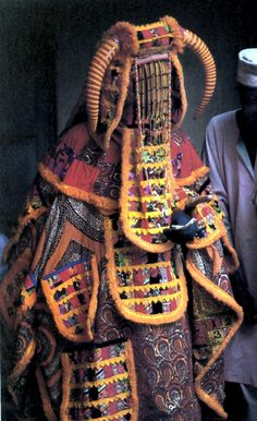 """Venezuela - Egungun costume. Multiple layers of cloth, medallions, and glass beaded veil. Photograph by M.T. Drewal. 1986.  Egúngún es una parte del panteón de la mitología yoruba. En la tradición Orisha y la adoración de los antepasados, el Egúngún representa """"el espíritu colectivo"""" de los antepasados."""