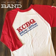 KCBQ Country Radio Raglan Tee KCBQ San Diego Country Radio raglan tee. Says KCBQ down right sleeve, text is slightly pink. There is a small red smudge shown in photo three. Looks like the red dye bled in the wash. Cool & unique tee!   BRAND: MATERIAL: 50/50 YEAR/ERA: early 80s LABEL SIZE: BEST FIT:   MEASUREMENTS: Chest  Length   ☠ No trades please!  Check out my closet for more vintage tees! Vintage Tops Tees - Long Sleeve