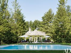 The poolhouse is surrounded by towering pines | archdigest.com