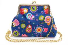 Lovely matryoshka pattern was mixed with recycled jeans fabric. The back side of the bag can be different color/pattern and  you choose the lining color if you like. It is padded inside. It has been sewn to metal clutch frame and comes with chain. Size: 13 x 19 cm