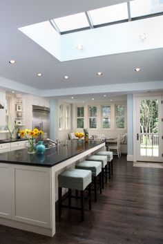 kitchen - dark wood floor, white cabinets, black counter tops