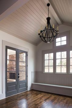 Gray cottage mudroom features a gray shiplap vaulted ceiling accented with an iron chandelier illuminating a gray beadboard window seat bench across from black glass paned doors.