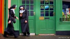 A nun is standing outside a pub ...