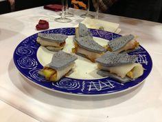 Tapa presentada por Taberna de Doña Casta, sandwich relleno de berenjena, carpaccio de bacalao y salsa romescu, todo ello entre pan de olivas