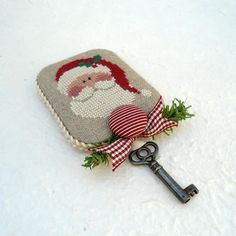 It is said that for those without a chimney, placing a magical Santa key outside the door will allow Santa to enter the home of good boys and girls. An heirloom keepsake piece has been created to do just that.    A wonderful old world cross stitched Santa design has been finished as a fob for Santas magical key. Santa has been stitched on a natural colored linen in a beautiful array of seasonal colors before being mounted on lightly padded mat board. The back has been wrapped in a simple…