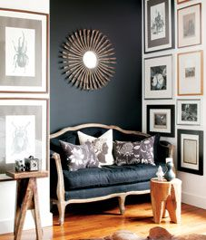 Black settee  A black linen-covered settee, with its curvaceous, feminine lines, has a softening effect in the master bedroom, and the mirror adds a bit of glamour. The chalkboard-painted focal wall lends a sense of balance and anchors the light-filled space.