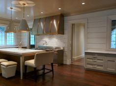 Turner Davis Interiors.    white & gray beautiful kitchen design with light gray kitchen cabinets, stainless steel hood and appliances, kitchen island, calcutta marble counter tops & backsplash , gray cone pendants chandelier, tan storage ottomans with nailhead trim and pot filler.
