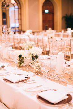 Gold Tiffany chairs, table runner and small white floral arrangements at this ballroom reception | Eugene and Pearlyn's Elegant Wedding at Four Seasons Hotel