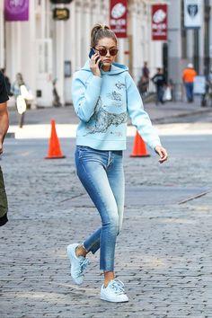 Gigi Hadid wears sweatshirt, cropped jeans, and blue sneakers