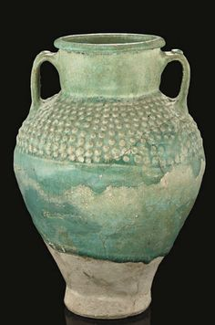 A KASHAN TURQUOISE GLAZED STORAGE JAR, IRAN, 12TH CENTURY Of high waisted form, two handles either side from neck to shoulder, with moulded globular decoration in a band to shoulder - 10 1/2in (26.5cm) high
