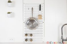 Wall Control Metal Pegboard to hang cookware and utensils, as well as hang magnetic spice jars.