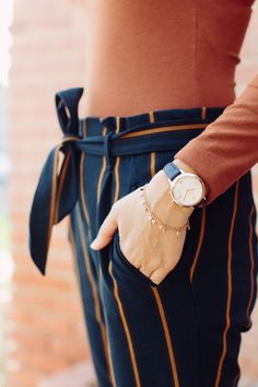 rust bodysuit, navy striped trousers and navy watch