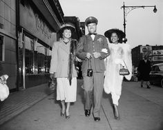 An Easter Sunday stroll by the Hotel Theresa in Harlem: Air Force Sergeant Harry Logan escorts his wife (right) and Jean Leonard, both of whom are in their Easter finery on April 13, 1952.