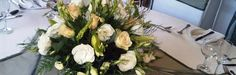 Large, low bouquets of massed flowers provide drama but allow guests to have unlimited views of the festivities. Via The Ultimate Wedding Flower Guide on FloristChronicles.com.