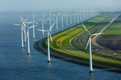 Flanked by windmills, this dike protects farmland that is almost entirely below sea level in Flevoland, the Netherlands.