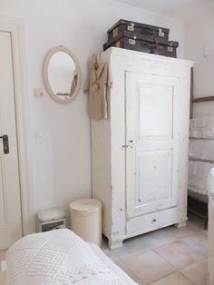 white armoire + suitcases + mirror