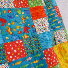 Sea Shanty Quilt Kit : The Sea Shanty quilt is a bright and cheerful children's quilt featuring a whole host of denizens of the deep – whales and dolphins, sea turtles, seahorses, starfish and crabs, as well as sea shells and lots of fish. The design is based on small and large squares so it's straightforward to piece, and the turquoise, yellow, orange and green palette makes for a really zingy quilt that'll brighten the face of any young beachcomber or budding marine biologist.
