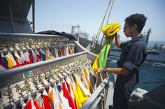 Quartermaster Seaman Arielle Cox, from Athens, Tenn., stows the preparatory signal flag aboard the guided-missile destroyer USS Arleigh Burke during a replenishment at sea