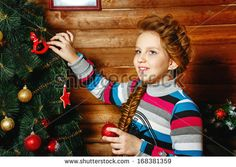 Little girl with plait Christmas tree decorates toys @shutterstock