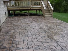 stamped concrete patio coming off of a simple deck. Just needs firepit.