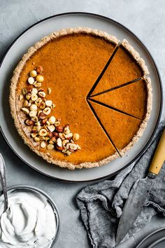 Creamy and smooth gluten-free dairy-free pumpkin pie with a crumbly hazelnut pastry tart crust. Top it with whipped coconut cream and toasted hazelnuts. This is the best pumpkin pie, hands down! #tart #pie #pumpkinpie #pumpkin #recipe #glutenfree #dairyfree #thanksgiving #dessert