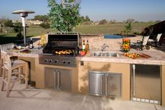 As part of a sprawling patio connected to a pool and jacuzzi, this outdoor kitchen stands with stainless steel cabinetry and appliances, granite countertop, and plenty of space for barstool seating.