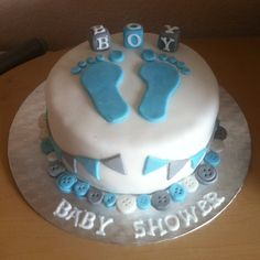 Baby boy baby shower cake with fondant footprints, blocks, bunting and buttons