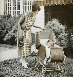 A mother holding a Kodak camera and her young child asleep in a pram, 1924. #vintage #1920s #ads