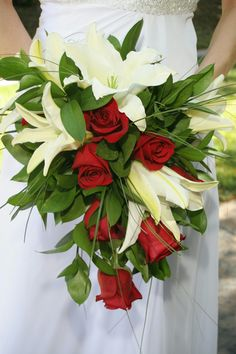Beautiful Cascading Bridal Bouquet Showcasing: White Casablanca Lilies, Red Roses + Several Varieties Of Greenery & Foliage Red Flower Bouquet, Red Flowers, Red Roses, Casablanca, Orange, Yellow, Lilies, Wedding Bouquets, Greenery