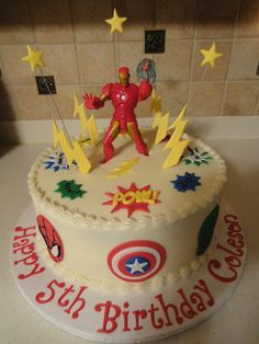 Super Hero Cake with Captain American, Spiderman, Superman, Flash, Batman, Iron Man and Hulk going around the side of the cake.