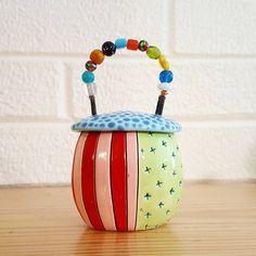 Teeny tiny pot with beaded handle.