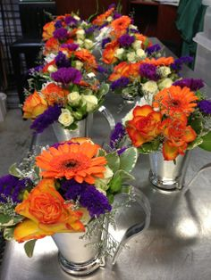 Church pew flowers of bright orange and purple flowers in silver mint julep cups are ready to be hung on the pews. Following the ceremony, remove the handles and you have the perfect cocktail table centerpiece, at the perfect price! Flower by Seasonal Celebrations. http://www.seasonalcelebrations.com