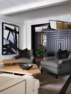 Living room with gray armchairs, a large black cabinet and modern art