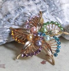 Very pretty multi colored - crystal gem - pin wheel style vintage pin. Pastel colors of green...