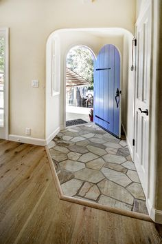 Beautiful blue, arched, entry door.  stone entry way