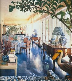 Blue and white sunroom. I have this picture in one of my decorating books. The floor is painted concrete and scored to create the pattern.