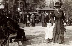 Artis. Bezoekers van de dierentuin. Op de voorgrond een dame met hoed en in lange kleding, samen met een peutertje. Amsterdam, 1910.