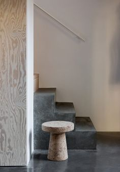 A concrete staircase leads to the upper level of this house, where wooden boards provide flooring. Here, a small study is set in an alcove alongside two bedrooms, with furnishings including a splattered stool by Max Lamb.