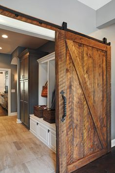 Sliding doors, like this handhewn barn door made from reclaimed lumber, can hide mudrooms