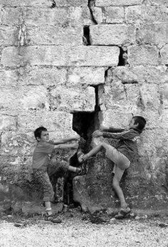 This photo is unique because of the perspective it uses. Even though, the two boys are not actually pulling the brick wall apart, their actions make it look like they are.