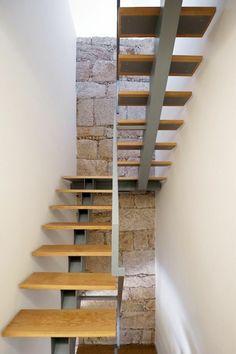 escalier bois, escalier limon central, escalier flin, métal au centre en couleur grise, murs en cailloux rudes blancs et gris, appartement dans un style rustique et industriel