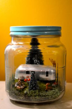 Miniature Spring Airstream Scene with deer, pine trees, mushrooms, and campfire, and LED lights in glass jar with painted blue lid