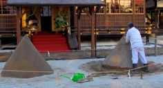 While visiting Kamigamo shrine (上賀茂神社) in Kyoto, yesterday a shrine attendant was constructing a Tatesuna (立砂) in front of the Sai-Den. Tatesuna (立砂) are a pair of standing cones of sand in front of Sai-Den at Kamigamo-jinja. They are traditionally construed as allusions to a pair of sacred mountains.