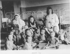 "Kovno, Lithuania, Three nurses with a group of children in a ghetto orphanage, 1941-1944.  After the parents were massacred, the Germans sent nurses to treat the orphaned children and turned the place into a ""children's division hospital"", when in fact it was an orphanage."
