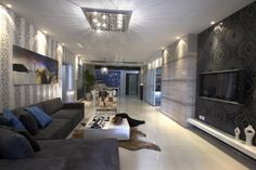 Long sleek living room with light floor, dark grey sofa, black wall and white ceiling with silver fixtures