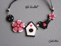 Un collier composé de deux fleurs, d'un oiseau et d'une nichoir rose corail, noir et blanc en pâte polymère par Clafoutine