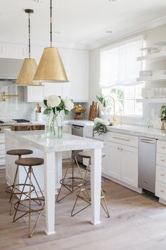Two Goodman Hanging Lamps in Antique Brass stands over a white kitchen island topped with gray and white quartzite lined with round brass and wood counter stools, Arteriors Wyndham Swivel Counter Stools.