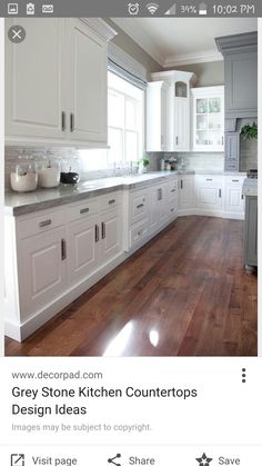 Medium wood floors in kitchen with white cabinets