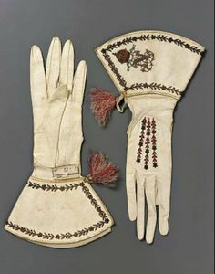 "1825-1850 French Women's gloves at the Museum of Fine Art, Boston - From the curators' comments: ""Pair of women's gloves, possibly made for the Empress Eugenie. White leather, embroidered on back of hand and on gauntlets with tarnished metal thread, and red silk. An ""N"" surmounted by an imperial crown on each gauntlet. Tassels of red and white silk at each wrist."""