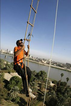 We'll take the elevator, thank you: A window washer climbs a rope ladder hanging from a hotel along the Tigris River in Baghdad.